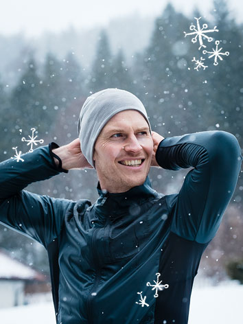 A smiling man putting on a beanie as he gets ready for a run in the snow.