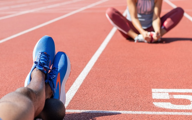 two runners sitting on a track stretching
