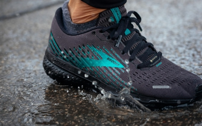 Close-up of a black and green running shoe as a runner steps on wet concrete.