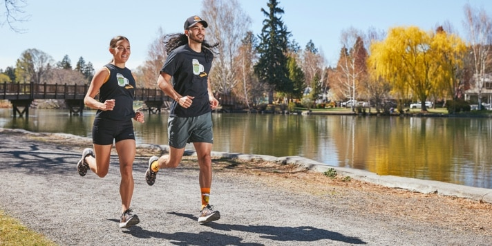 2 runners running by a river