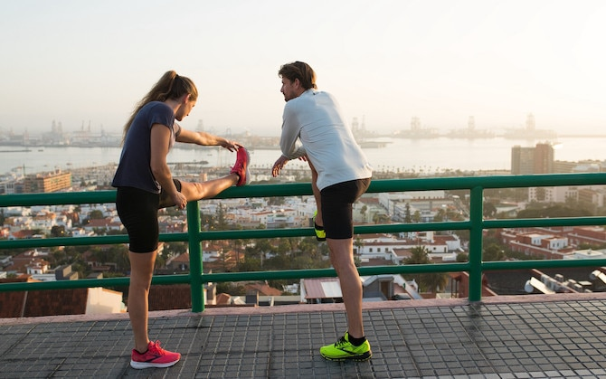 Two runners use a fence to help stretch after running.