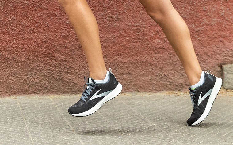 A runner toes off in black and white Revel shoes.