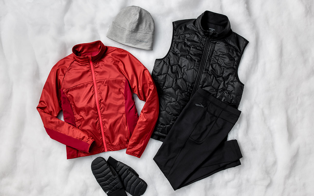 A styled photo of gear, clockwise from top: Notch Thermal Beanie, Shield Hybrid Vest, Momentum Thermal Tight, Cascadia Thermal Mitten, Fusion Hybrid Jacket