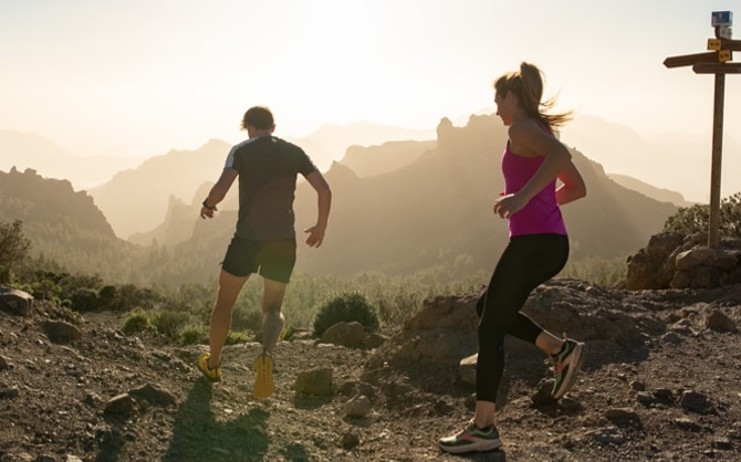 Two runners running in the mountains