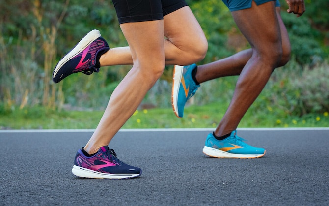 Two runners with their feet striking the ground