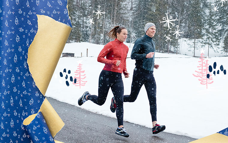 Photo of a man and woman running on a road with snow in the background