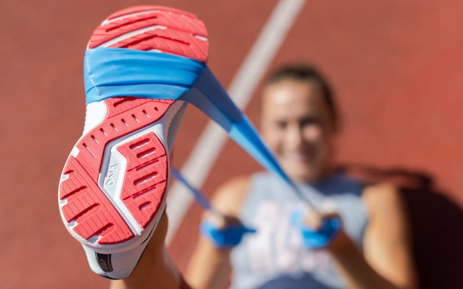 Runner using a stretch band around the bottom of her foot