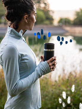 A woman holding a coffee tumbler looks out at a lake.