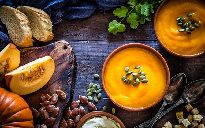 A top-down photo of two bowls of pumpkin soup topped with pumpkin seeds, surrounded by fall slices of rustic bread, a pair of spoons, a smattering of croutons, a sprig of cilantro, and sliced and whole pumpkin.