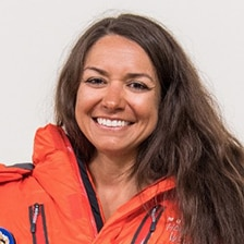 A profile photo of the author, Roxanne Vogel, smiling widely in a bright orange jacket.