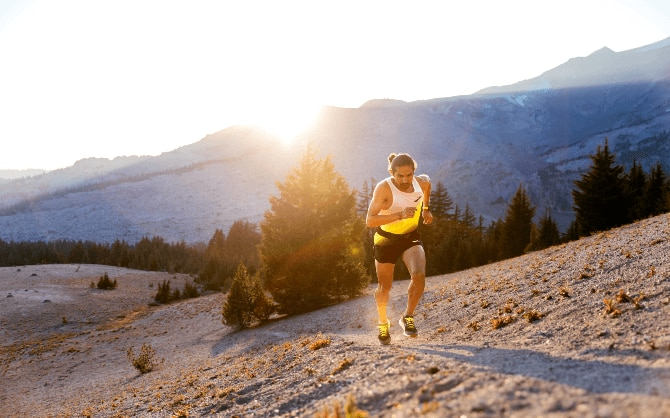 Man running up a steep trail