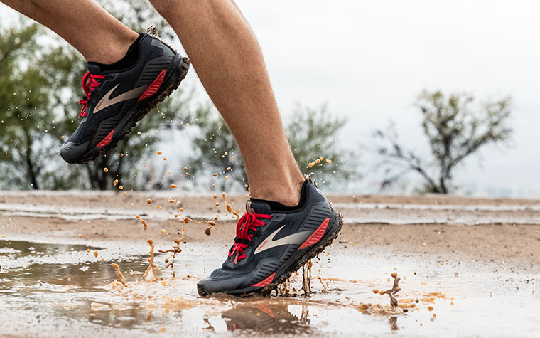 Close-up of runner's feet going through mud puddles in the Cascadia GTX.