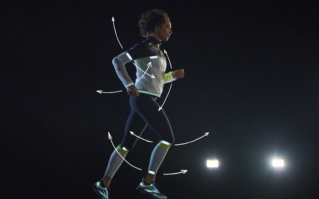 A runner in Run Visible gear is shown against a black background, with arrows tracing motion paths for critical motion zones on the body.
