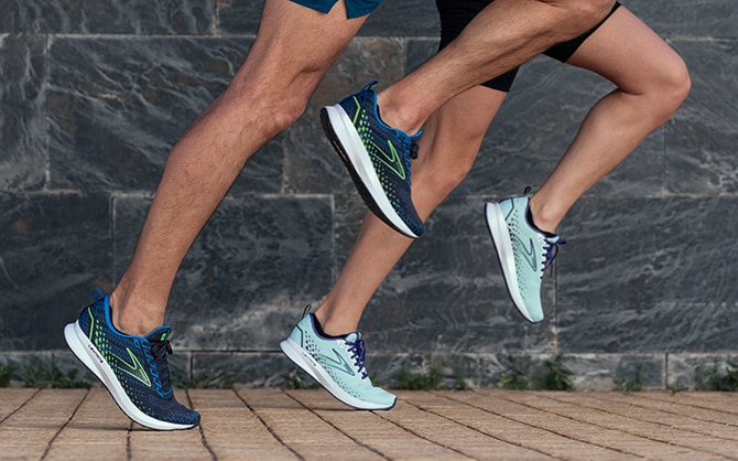 Two runners stride forward in unison