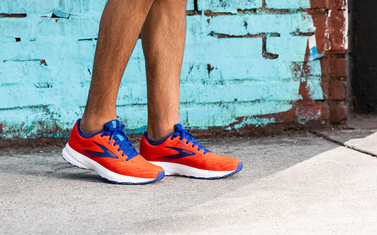 Runner standing in front of a blue wall wearing the Launch in a bright red colorway.