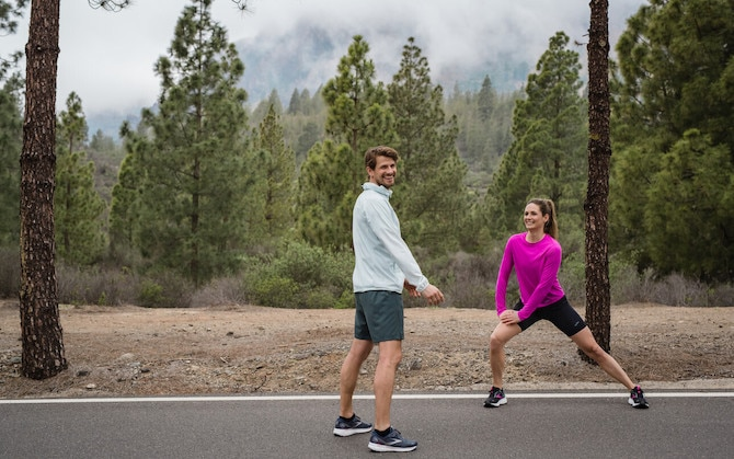 Two runners perform dynamic exercises to warm up before running.