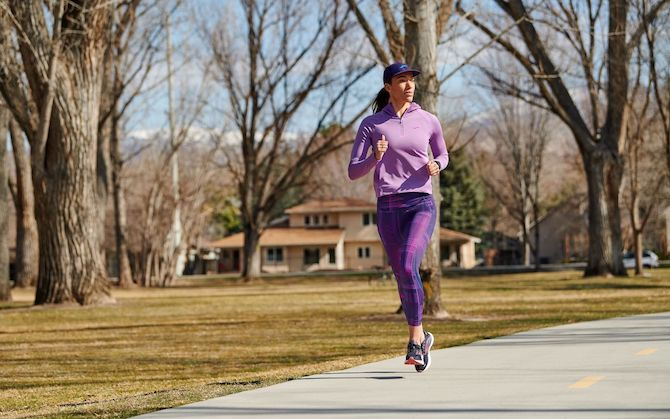 A runner jogs through a wooded residential neighborhood.