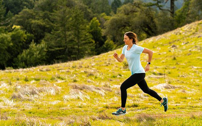 Woman running through mountain meadow