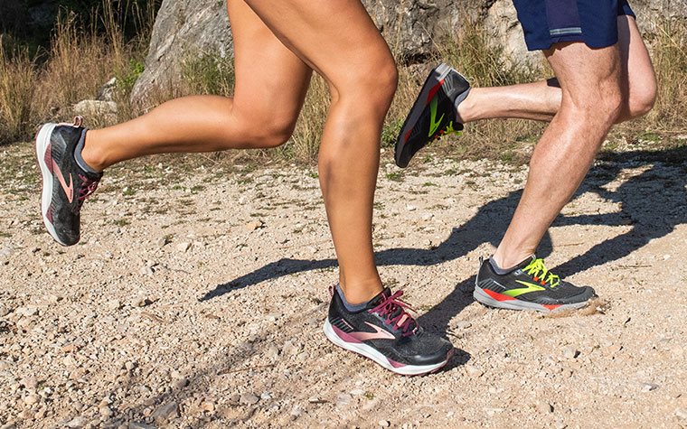 Close-up of two runners' legs in the Cascadia, striding along a trail.