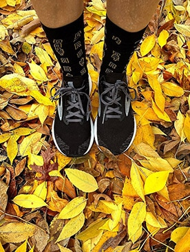 A detail photo of a runner sporting Thanksgiving themed socks while standing on gold fallen leaves.