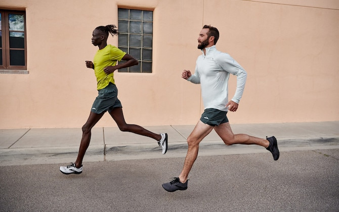 Two runners run side-by-side on a city road.