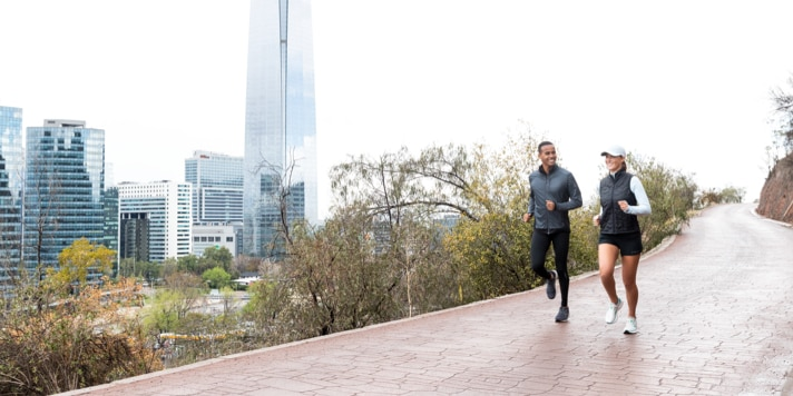 Two runners head out together on a peaceful path outside a city.