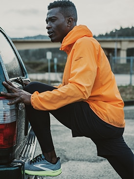 Runner stretching on a car