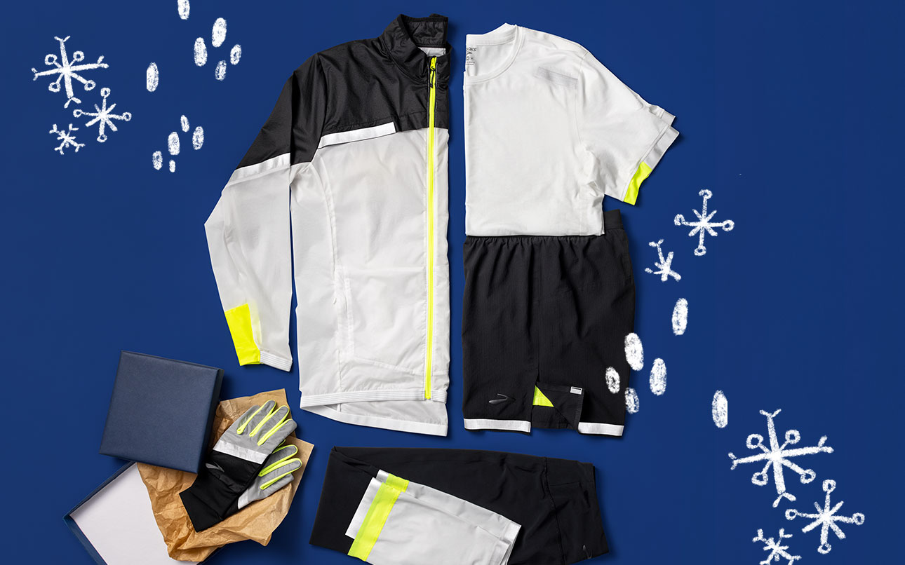 """A styled grouping of Run Visible gear, including clockwise from top, Men's Carbonite Jacket (black and white with reflective strips), Men's Carbonite Short Sleeve (white with reflective strips), Men's Carbonite 7"""" 2-in-1 Short (black with reflective strips), Unisex Carbonite Glove (black and white with reflective strips), Men's Carbonite Tight (black and white with reflective strips)"""