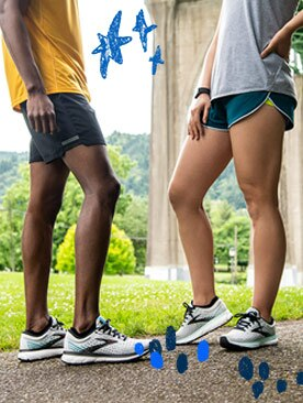 A man and woman pose in running shorts and light, warm weather shirts.