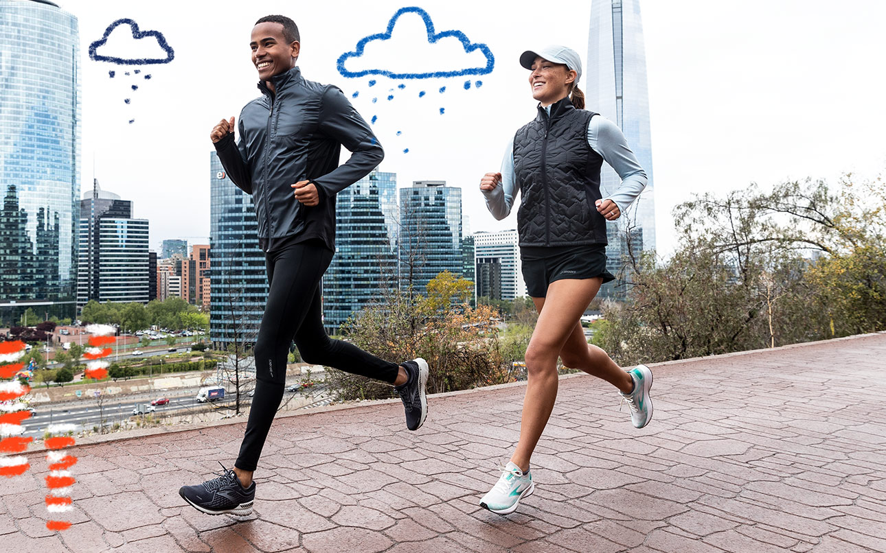 A man and woman run in cloudy weather with a cityscape in the background.