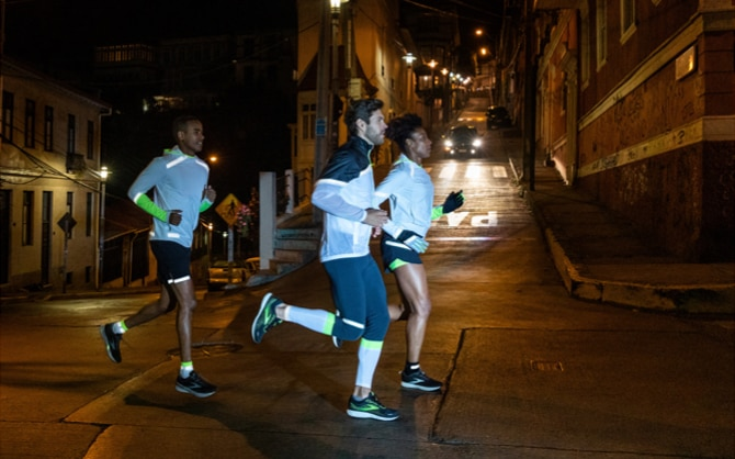 Three runners cross a road at night, all wearing Run Visible gear.