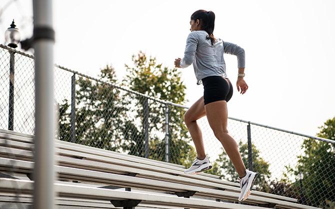 Women running up bleacher steps.