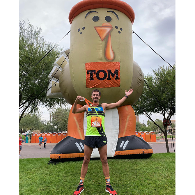 """A male runner poses with a medal in front of a giant inflatable turkey that is wearing a sign that says """"Tom."""""""