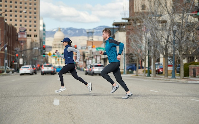 Side view of two runners mid-stride while running on a city street.