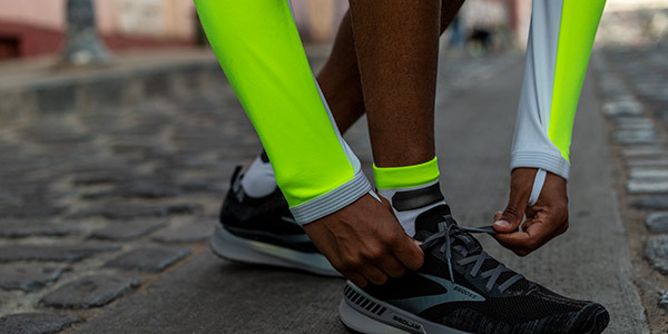 A closeup shot of a runner wearing Brooks Nightlife Collection gear and stooping over to tie his shoes.