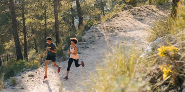 Two runners team up for a long run through a forested area.