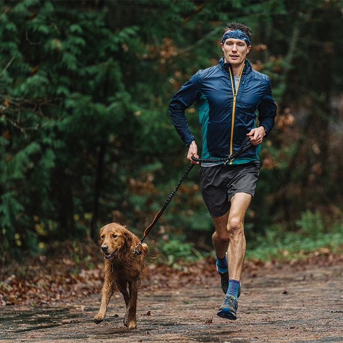 Man running down a trail with his dog
