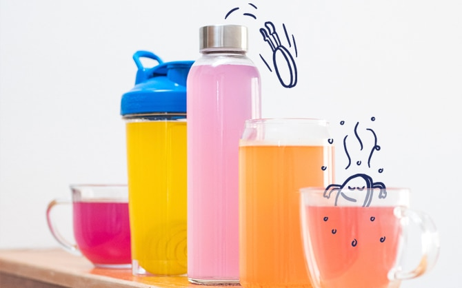 Different cups and bottles with pink, orange, and yellow liquid