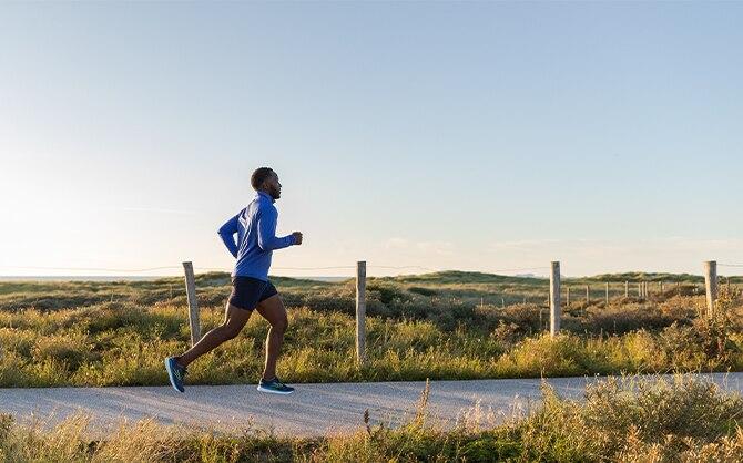 Man runs on a trail through a meadow.