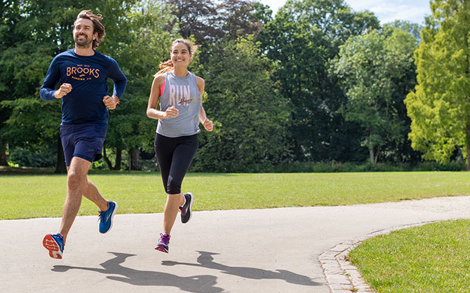 Two runners mid run on a paved path in a park.