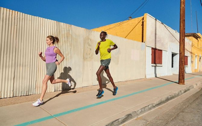 Two runners on a sunny sidewalk in a city.