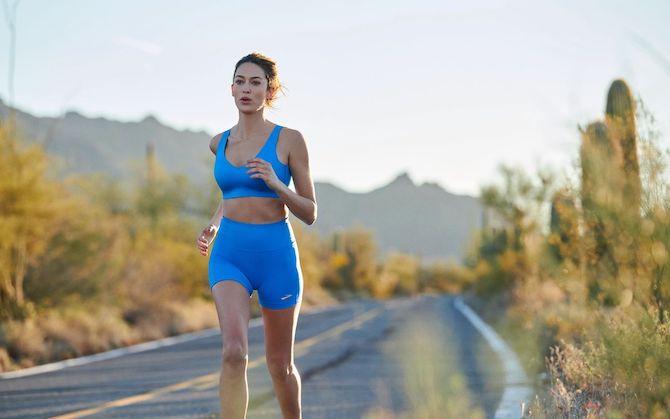 A runner on a desert road during a hot summer day.