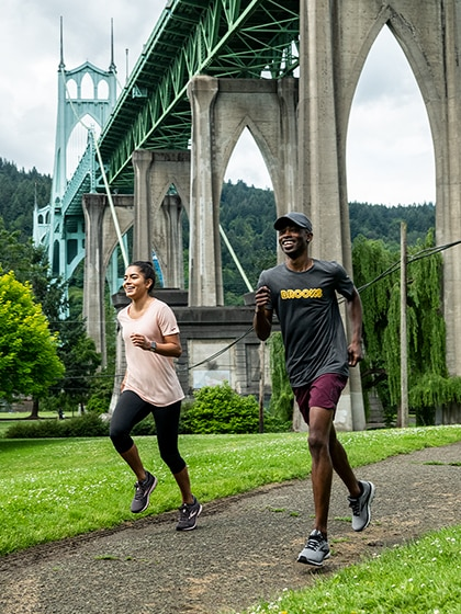 Two people run on a grass-line trail with a big bridge in the background.