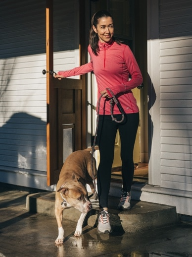 Woman walking out the door with her dog