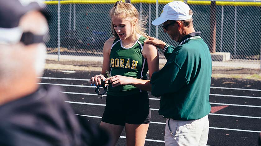 Tim Severa talking to a student athlete; they are standing together on a track and the student's uniform reads 'Borah'.