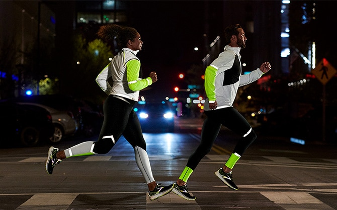 Side view of two runners running in the dark