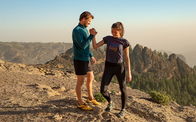 A man and a woman wearing the new Cascadia 16 in the mountains