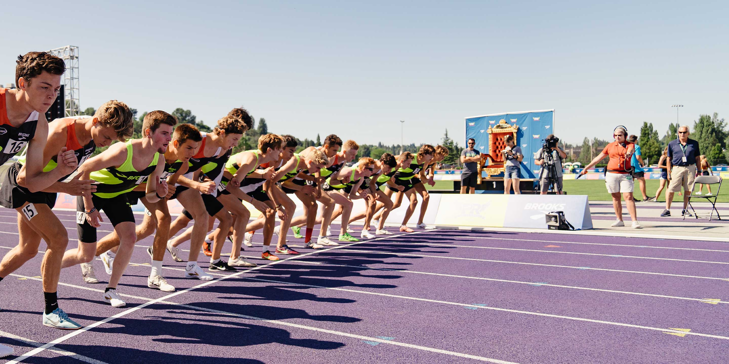 Athletes lined up on the track on a sunny day