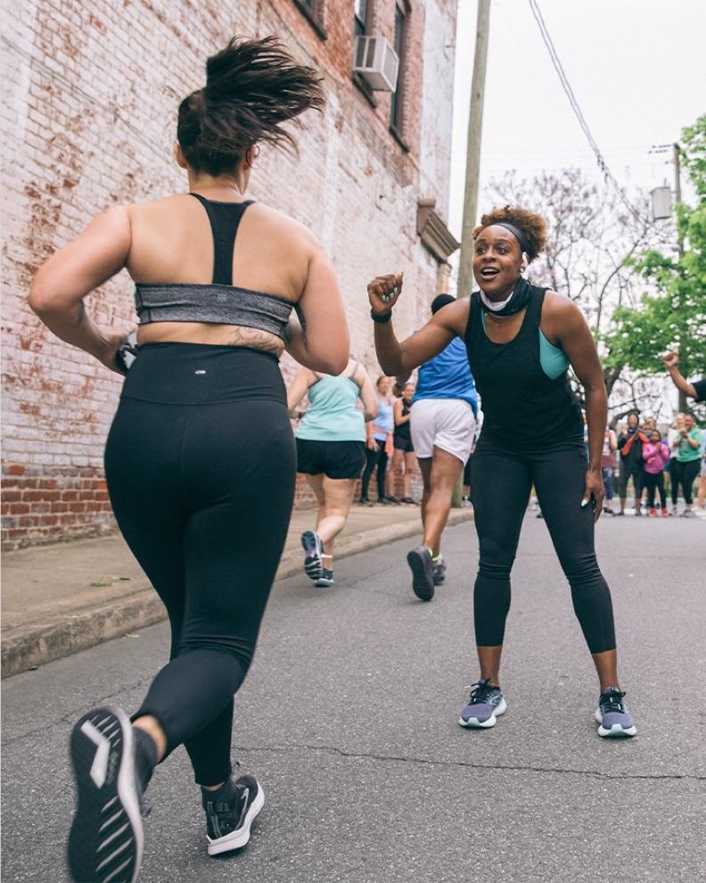A woman high fiving runners