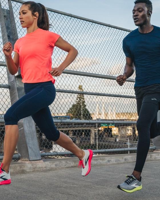 A man and woman running across a bridge.